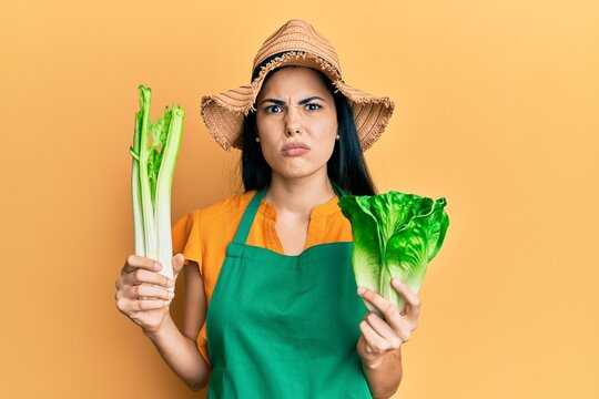 Beautiful young woman wearing gardener apron holding vegetables skeptic and nervous, frowning upset because of problem. negative person.
