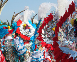 Colorful carnival background with bright feather headdresses.Small parade of dancers in festival costumes who celebrate Carnival in the streets.