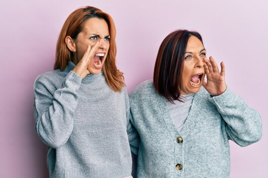 Latin mother and daughter wearing casual clothes shouting and screaming loud to side with hand on mouth. communication concept.