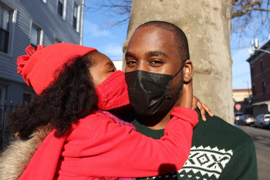 Black child kissing father wearing red and green Christmas colored winter clothing and masks