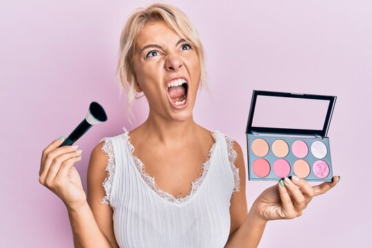 Young blonde girl holding makeup brush and blush angry and mad screaming frustrated and furious, shouting with anger looking up.