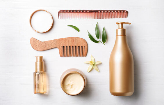 Flat lay composition with hair cosmetic products on white wooden table