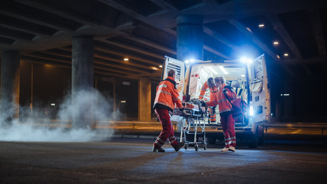Team of EMS Paramedics React Quick to Bring Injured Patient to Healthcare Hospital and Get Him Out of Ambulance on a Stretcher. Emergency Care Assistants Help Young Man to Stay Alive After Accident.
