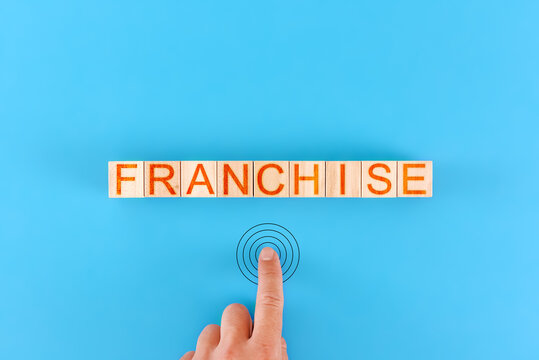 man presses the drawn button next to the word franchise made up of wooden blocks
