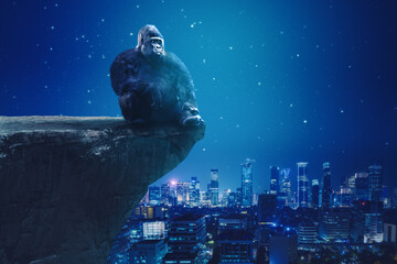 Gorilla sitting on cliff with glowing city background