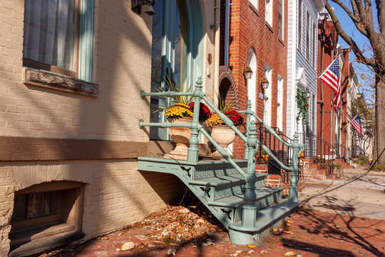 View of the old town historic district of Alexandria, Virginia with vintage 19th century brick townhouses. They have metal stairs on the front and a small porch with room for a few potted flowers.