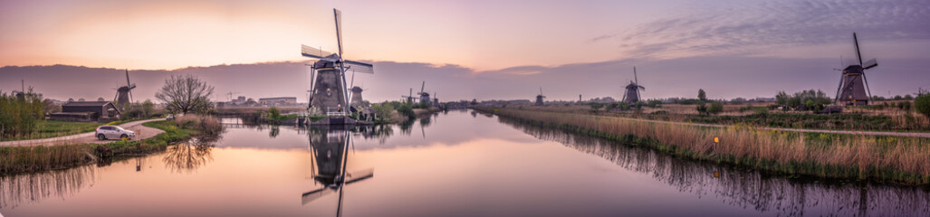 Traditional dutch scenery panorama with windmills at sunset. Netherlands countryside