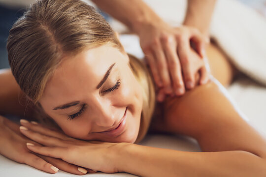 Professional masseur doing therapeutic massage. Woman enjoying massage in her home. Young woman getting relaxing body massage.