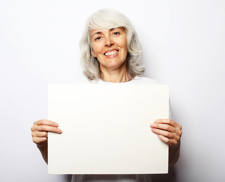 Portrait of happy senior woman with blank advertising board or copy space