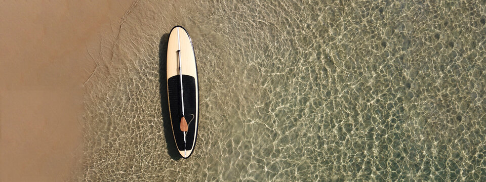 Aerial drone top down ultra wide photo of Stand Up Paddle surf board or SUP board as seen in tropical exotic beach shore