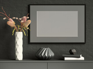Black mock up picture frame on dark plaster wall with white ceramic vase with flowers, books and geometric pots; landscape orientation; stylish poster mock up background; 3d rendering, 3d illustration