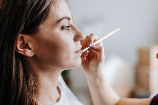 makeup artist applies lip gloss at a beauty salon.