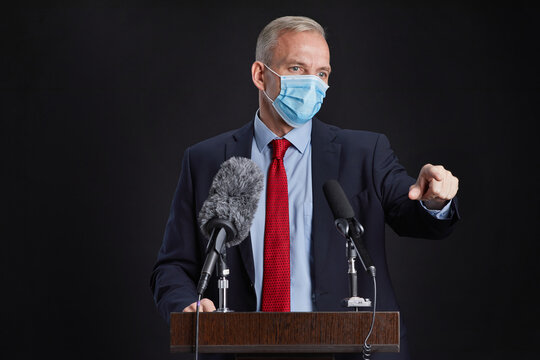 Waist up portrait of mature man wearing mask and gesturing while giving speech standing at podium against black background, copy space