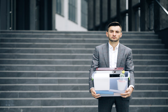 Businessman gets fired and walking near office center with box documents. Lost His Job. Unemployment rate growing due pandemic. Male office worker in despair lost job