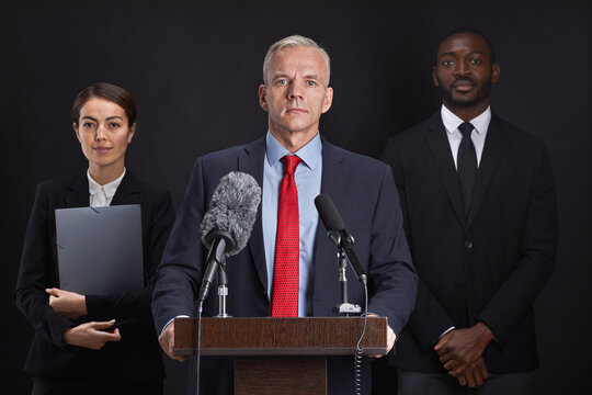 Waist up portrait of mature man giving speech standing at podium with two assistants in background