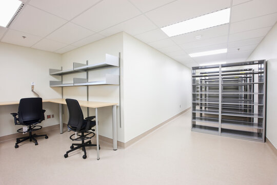 Empty office with desks chairs and server towers.