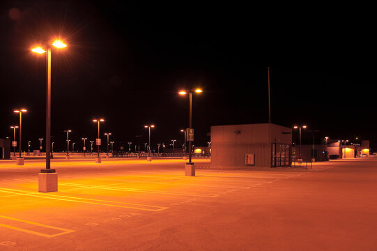 Empty parking lot with street lights at night.