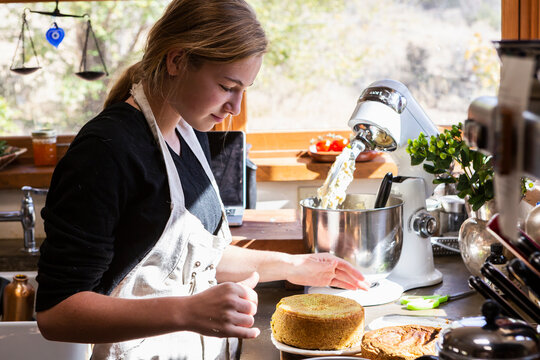 Teenage girl in kitchen baking a cake.