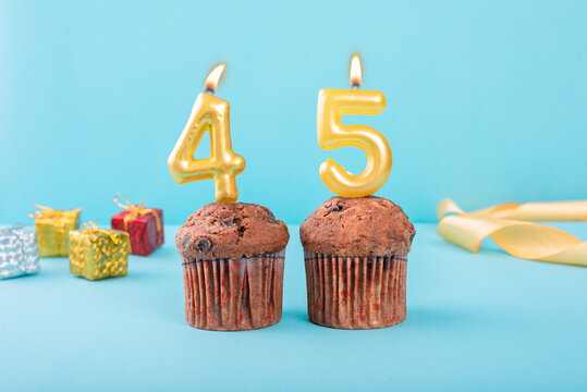 45 Number gold candle on a cupcake against a pastel blue background forty fifth year celebration