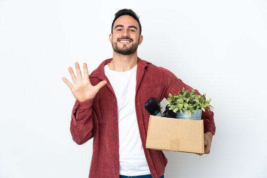 Young caucasian man making a move while picking up a box full of things isolated on white background counting five with fingers