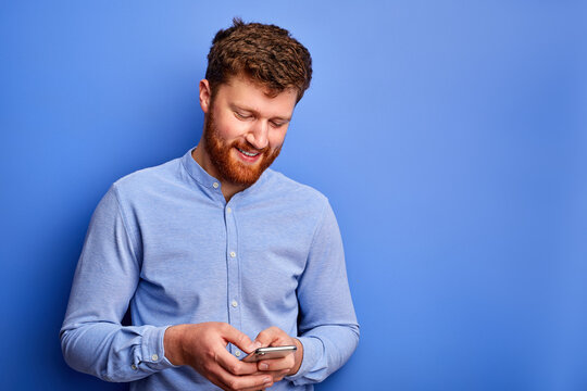 smiling bearded man is chatting with someone on smartphone, looks at screen of mobile phone, isolated over blue background