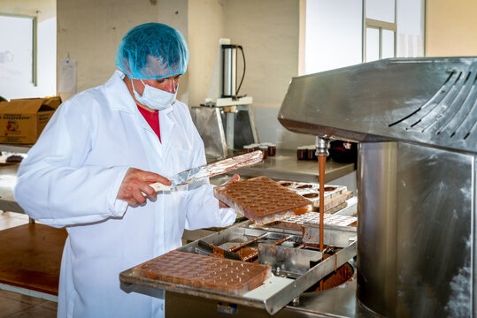 Guaranda, Bolivar / Ecuador - November, 2013: A worker at a local chocolate factory, in a white coat, head and face protector, producing a daily chocolate batch.