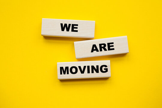 WE ARE MOVING inscription on CUBES , yellow pen on a yellow background. a bright solution for business, financial, marketing concept
