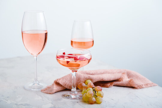 Rose wine in different types of glasses on light concrete background with grapes. Wine composition on white table with copy space