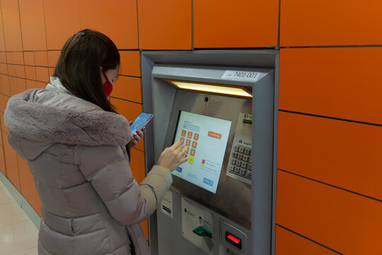A girl in a winter jacket and a protective face mask receives a parcel at the packstation. Non-contact delivery. Shopping during a pandemic. The girl enters the order code at the automated packstation