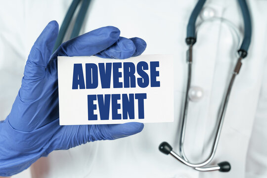 The doctor holds a business card that says - ADVERSE EVENT