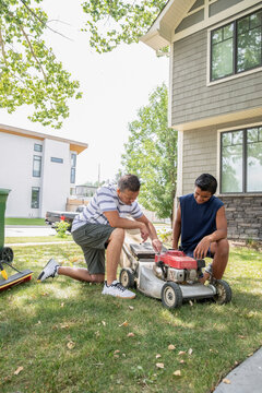 Father and son fixing lawn mower in garden