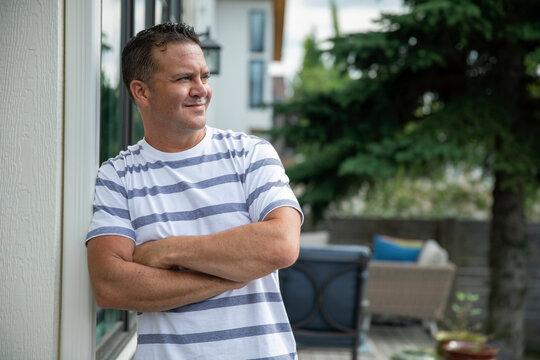 Portrait of man leaning on wall in backyard