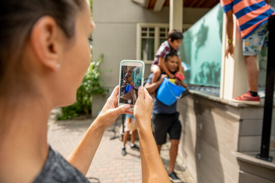 Woman taking photograph of husband and sons cleaning house exterior