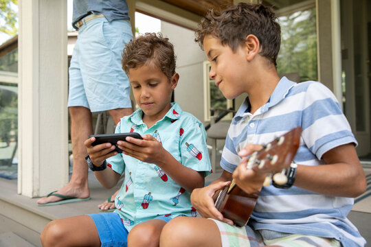 Boys with ukulele looking at phone