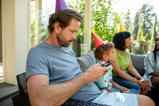 Man wearing cone hat looking at phone at birthday party