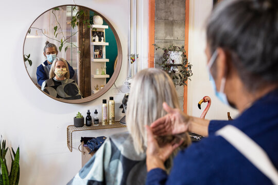 Hairdresser in facemask attending to customer in startup salon