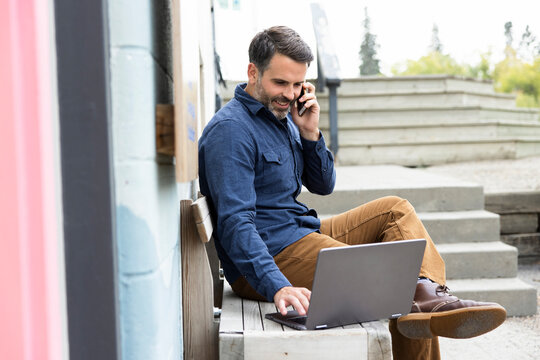 Startup owner working on digital devices outside building