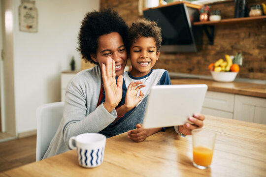 Happy African American mother and son waving during video call at home.
