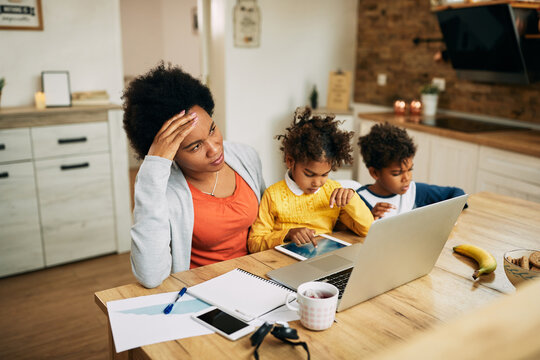 African American single mother feeling stressed out while working at home.