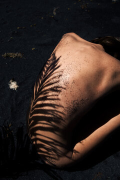 woman's back with shadows of palm sitting on the beach with black sand