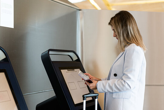 woman using the check-in machine at the airport getting the boarding pass.