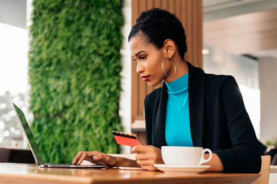 Afro woman using cellphone and credit card