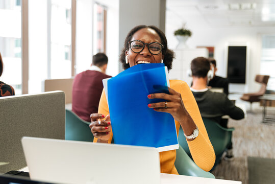 Positive woman laughing while working with laptop and documents at office