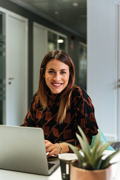 Content businesswoman with laptop at office