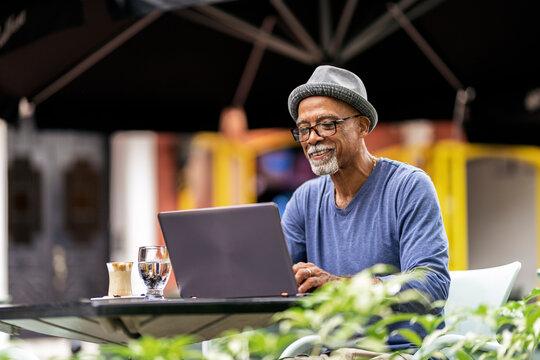 Senior black man using his laptop.