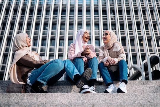 Three muslim women talking and laughing.
