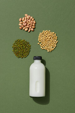 Tasty vegan milk on green table