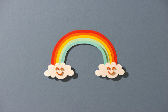 Cloud and Rainbow in blue sky Paper cut art Style the concept is season day