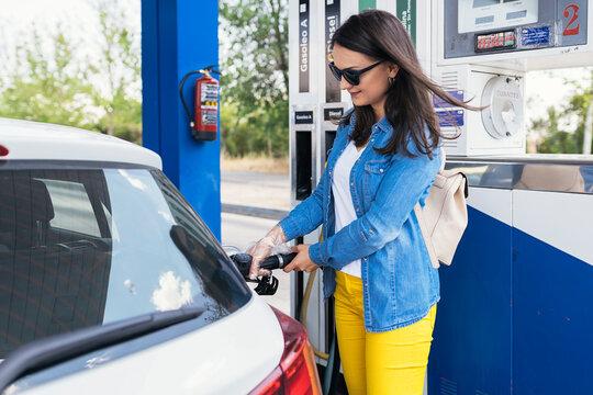 Beautiful woman filling the car's tank