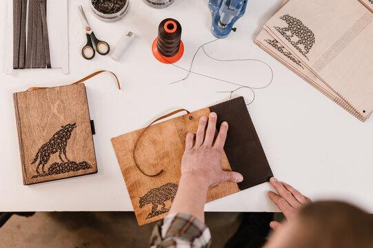 Crop craftsman creating notebook cover
